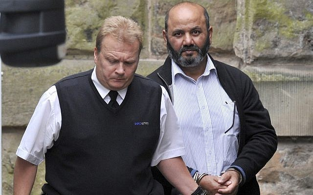 Iftikhar Ahmed, the father of murdered teenager Shafilea Ahmed being escorted into a British court on Friday Aug. 3, 2012 (photo credit: AP/Martin Rickett/PA)