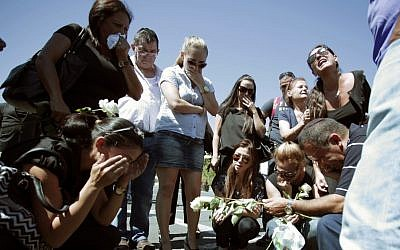 Relatives of five Israeli victims of a suicide bomber who targeted a bus of Israeli tourists a month earlier, mourn during a commemoration ceremony at Burgas airport, Bulgaria Wednesday. (photo credit: AP)