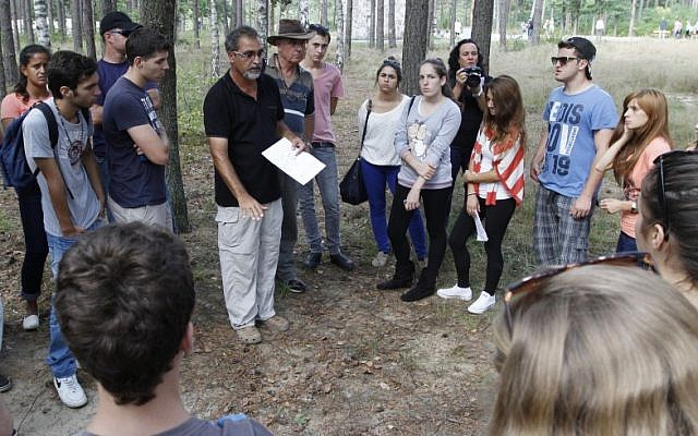 Archaeologist Yoram Haimi talking to young people from the Dror School in Israel about his findings at the site of the former German Nazi death camp of Sobibor, in eastern Poland, on Tuesday, Aug. 21, 2012 (photo credit: AP/Czarek Sokolowski)