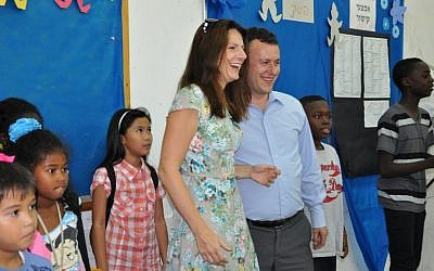 Britain's ambassador to Israel, Matthew Gould, and his wife, Celia, with some of the students of the Bialik-Rogozin school Tuesday. The British embassy hosted an Olympics celebration at the school and the kids, in turn, showed the ambassador how to play the Wii. (photo credit: Michal Shmulovich/Times of Israel)