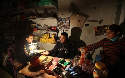 A Palestinian shopkeeper lights a gas lamp during a power cut at his shop in El-Shatea refugee camp western Gaza city in 2010 (photo credit: Wissam Nassar/Flash90)