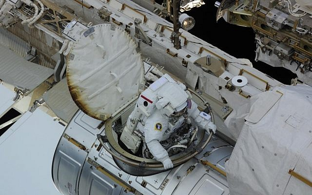 "Reflecting on his experience as he emerged from the craft into the daylight on the Expedition 24 mission's second spacewalk, astronaut Doug Wheelock said ""the colors of the Earth just explode at you as you exit toward the planet. Notice what looks like scorch marks on the hatch thermal cover, the effect of vacuum and atomic oxygen on the threads and thread sealant used on the thermal cover. The 'smell' of space follows suit, I've heard it described like burnt cake or cookies, or like the smell of an extinguished match."" (photo credit: NASA/Flash90)"