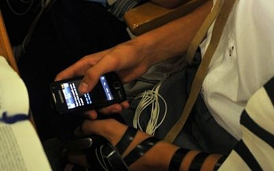 Young Jew plays on a cellphone in a synagogue during morning prayers. (Serge Attal/Flash90)