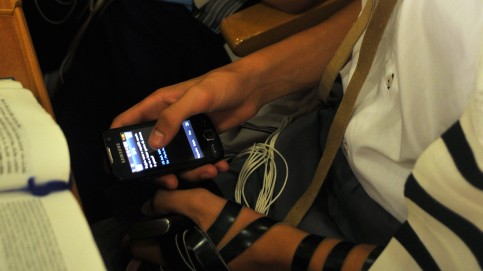 Young Jews play on a cellphone in a synagogue during morning prayers (photo credit: Serge Attal/Flash90)
