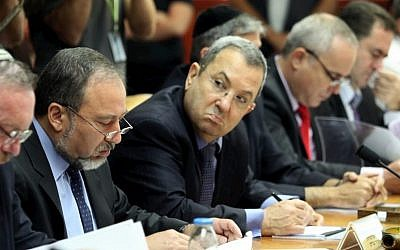 Defense minister Ehud Barak (holding pen) looks at foreign minister Avigdor Liberman (to his right) at a 2010 cabinet meeting. (Amit Shabi/POOL/FLASH90)
