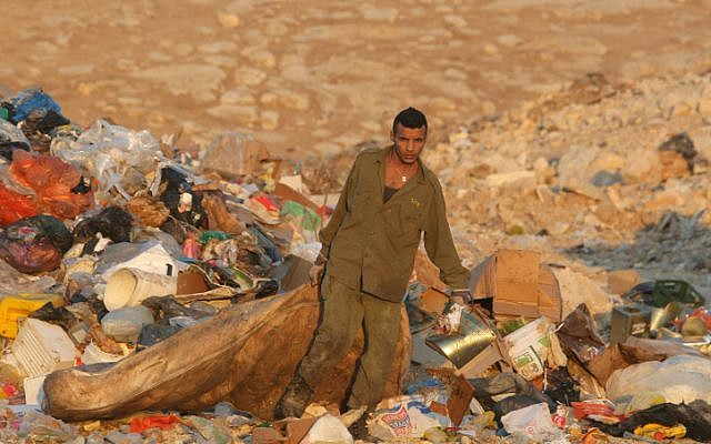 A Bedouin man with an IDF uniform drags a mattress as he looks for anything valuable at a garbage dump outside Jerusalem. (photo credit: Kobi Gideon/Flash90).