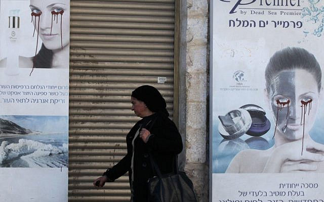A woman walks past a vandalized poster in Jerusalem, December 6, 2011. (photo credit: Yossi Zamir/Flash90)