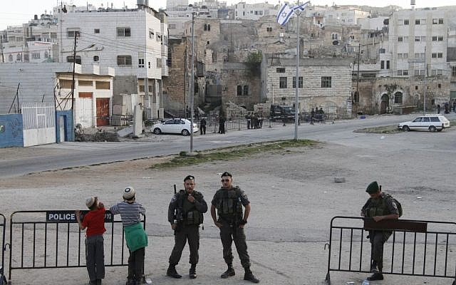 Jewish settlers and Israeli border policeman in Hebron (photo credit: Miriam Alster/Flash90)