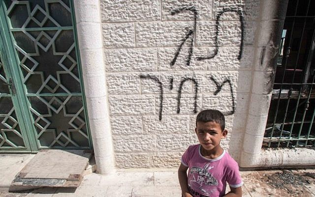 "A Palestinian boy stands in front of a mosque near Ramallah in June. The spray-painting behind him says ""price tag,"" referring to acts of vandalism by pro-settler extremists against Palestinians in the West Bank. (photo credit: Uri Lenz/Flash90)"