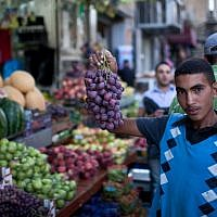 Illustrative: A Palestinian youth in Jerusalem displays his produce during Ramadan, July 24, 2012. (Noam Moskowitz/Flash90)