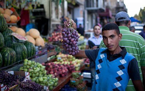Illustrative: A Palestinian youth in Jerusalem displays his produce during Ramadan, July 24, 2012. (Noam Moskowitz/Flash90)