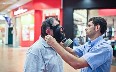 A man tries out a gas mask at an Israeli distribution center (photo credit: Noam Moskowitz/Flash90/File)