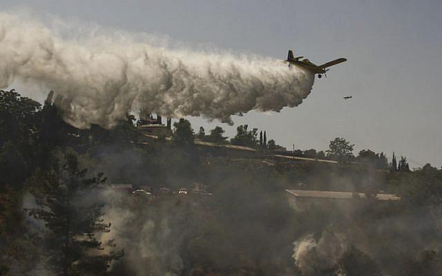 Firefighters work to extinguish a forest fire burning near Moshav Even Sapir. (photo credit: Oren Nahshon/Flash90)