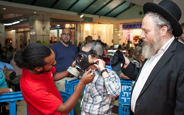 A postal worker helps a child try on a gas mask in Jerusalem. (photo credit: Noam Moskowitz/Flash90)