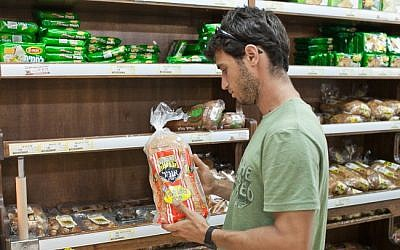 An Israeli chooses bread at a local store (photo credit: Noam Moskowitz/Flash90)