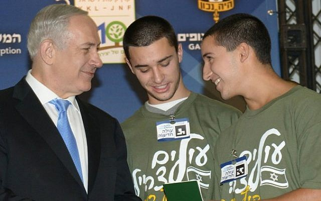 Prime Minister Benjamin Netanyahu presents Israeli identity cards to Barak and Ro'i Gaibel, one of five sets of twins that made aliya on Tuesday (photo credit: Amos Ben Gershom/GPO/Flash90)