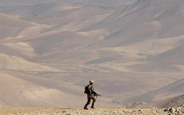 A soldier trekking through the desert in June. (photo credit: Moshe Shai/Flash90)