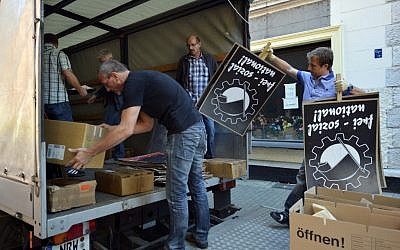 Police in plain clothes load into a vehicle items which they found in an apartment-sharing community of alleged neo-Nazis in Dortmund, Germany, Wednesday (AP/dapd, Sascha Schuermann)