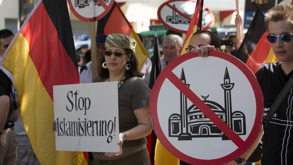 Demonstrators display signs with crossed-out mosques during a protest in front of a mosque in Berlin, Germany, Saturday. (photo credit: AP)