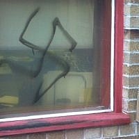 An illustrative photo of a spray-painted swastika on a window (ADL/JTA)