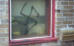 An illustrative photo of a spray-painted swastika on a window (photo credit: ADL/JTA)