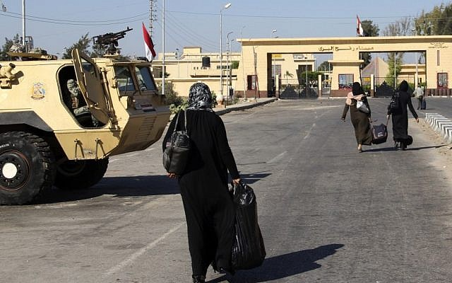 Palestinians walk toward the Egyptian border crossing with Gaza at Rafah, which has been temporarily reopened to allow the passage of Palestinians back to Gaza on Friday. Egypt closed the crossing in the wake of a deadly attack on Egyptian soldiers in the Sinai Peninsula that killed 16 troops (photo credit: AP)