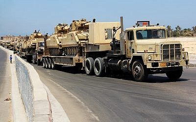Army trucks carry Egyptian military tanks in El-Arish, in the northern Sinai Peninsula (photo credit: AP)