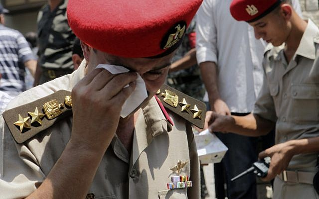 An Egyptian officer wipes his eye at the funeral of one of 16 soldiers killed in an attack over the weekend by suspected militants in Sinai (photo credit: AP/Thomas Hartwell)