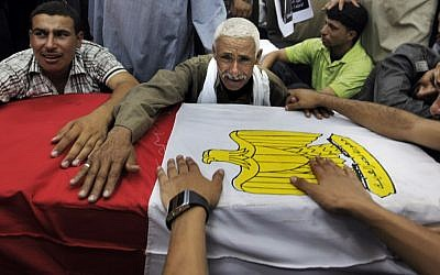 Relatives of slain Egyptian soldiers mourn during their funerals, July 7 (photo credit: AP Photo/Amr Nabil)