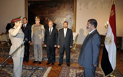 Then-Egyptian president Mohammed Morsi, right, swears in newly-appointed Minister of Defense, Lt. Gen. Abdel-Fattah el-Sissi, left, in Cairo in August 2012 (photo credit: AP/Egyptian Presidency)