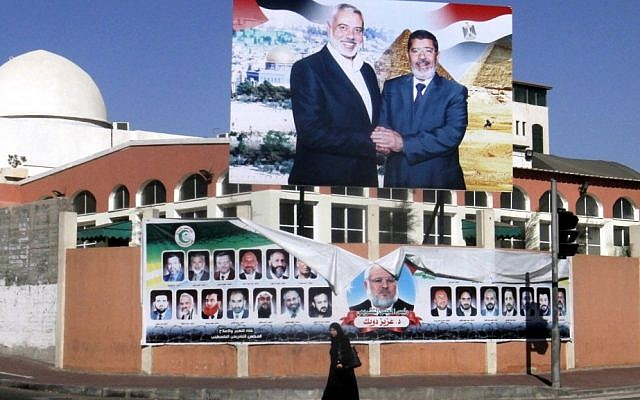 A Palestinian woman walks past a poster of Gaza's Hamas Prime Minister Ismail Haniyeh, left, and Egyptian President Mohammed Morsi in Gaza City, in August (photo credit: AP)