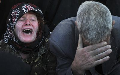 An Iranian woman and a man grieve after their loved ones were killed during Saturday's earthquake at the village of Bajebaj near the city of Varzaqan in northwestern Iran, on Sunday. (photo credit: AP/ISNA, Arash Khamoushi)