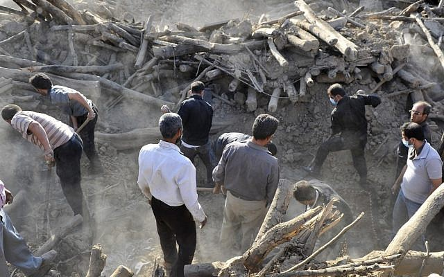 Iranians search the ruins of buildings after an earthquake in northwestern Iran, August 2012. (photo credit: AP/ISNA, Arash Khamoushi)