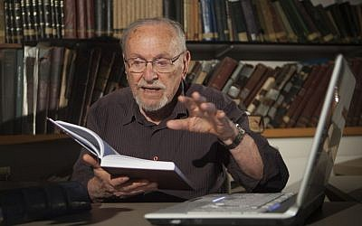 Biblical scholar Professor Menachem Cohen, reading from a book, at the Bar Ilan University library, outside Tel Aviv. (AP Photo/Dan Balilty)