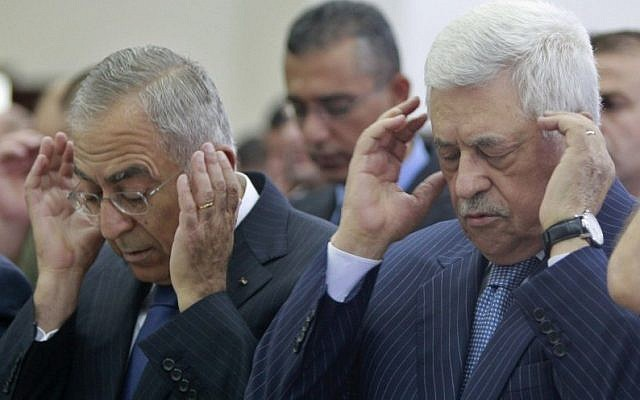 Palestinian President Mahmoud Abbas, right, and Prime Minister Salam Fayyad, left, attend prayers in Ramallah. (photo credit: AP)