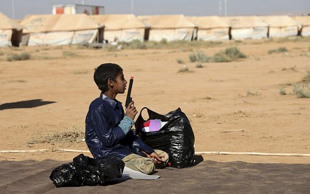 A Syrian refugee plays with a toy gun at Zaatari Refugee Camp in Mafraq, Jordan, Sunday, Aug. 19 (photo credit: AP/Mohammad Hannon)