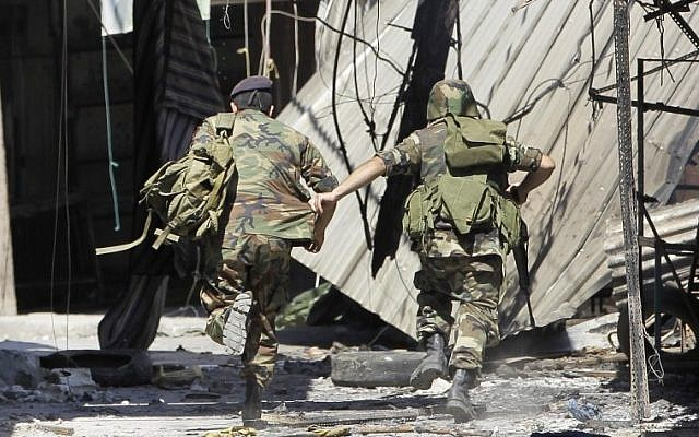 Lebanese army soldiers run from a sniper at an outdoor market in Tripoli in August. (photo credit: AP)