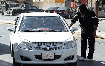 A masked man from a Sunni group who blocked a road linked to the Lebanese-Syrian border, checks a Syrian car which carries Syrian passengers, in Masnaa, eastern Lebanon, in August 2012. (photo credit: AP photo)