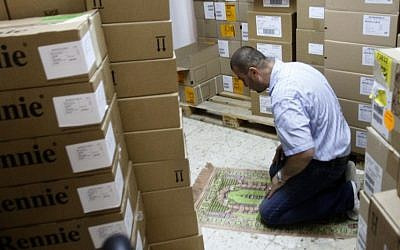 An employee of a Palestinian drug import company prays at the company's warehouse in the West Bank city of Ramallah. The cash crunch, mainly due to a sharp drop in foreign aid since 2011, is threatening to set off a chain reaction of business failures, layoffs and economic downturn that would undermine one of the West's fundamental strategies toward resolving the Israeli-Palestinian conflict. (AP Photo/Nasser Shiyoukhi)