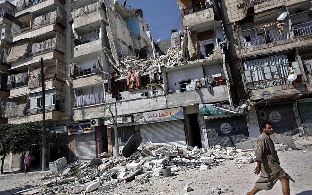 A Syrian man walks by a building destroyed in an airstrike in Aleppo, Syria on Aug. 17 (photo credit: AP/Khalil Hamra)