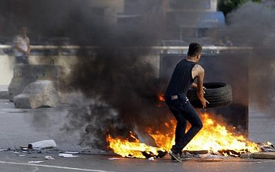 A Lebanese Shiite Muslim blocks the street in a southern suburb of Beirut, Lebanon, to protest against Syrian rebels' kidnapping of 12 Lebanese Shiite pilgrims in the Syrian northern province of Aleppo on Tuesday, May 22, 2012. (photo credit: Bilal Hussein/AP)