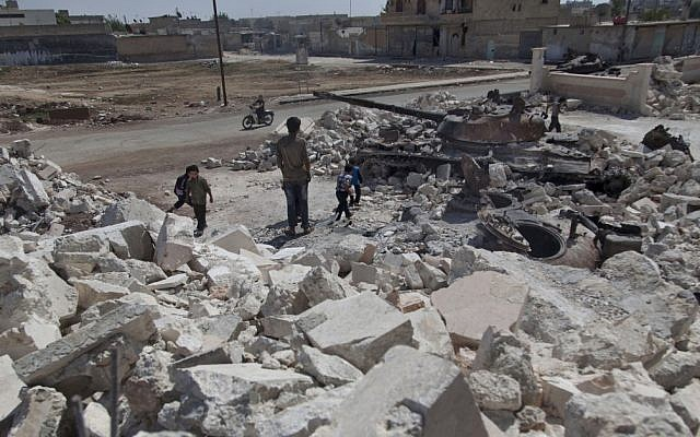 Syrian children play near a destroyed military tank next to the rubble of a damaged building in town of Azaz on the outskirts of Aleppo, Syria on Wednesday (photo credit: AP/Khalil Hamra)
