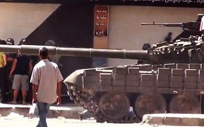 This image released by Shaam News Network purports to show a man walking past Syrian a military tank in Damascus, Syria. The Assad regime has allegedly been using heavy weapons against civilians. (photo credit: AP/Shaam News Network/AP video)