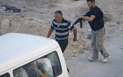 A Syrian rebel detains a man at an improvised checkpoint in a suburb of Damascus August 2 (photo credit: AP)