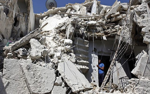 A Syrian man looks out of the rubble as rescuers, not shown, look for the bodies of two girls thought to be under the rubble of a building hit by a Syrian government airstrike in Aleppo in August 2012 (photo credit: AP/Khalil Hamra)