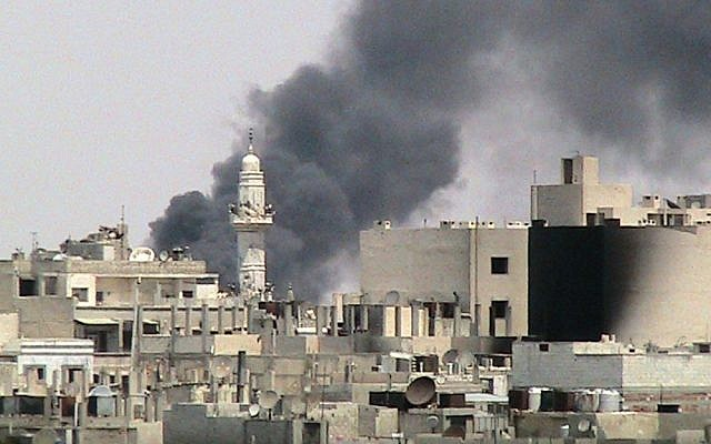 Illustrative: This image purports to show pillars of smoke as a result of shelling by Syrian government forces near al-Zafaran mosque in Homs, Syria, August 3, 2012 (photo credit: AP/Shaam News Network, SNN)
