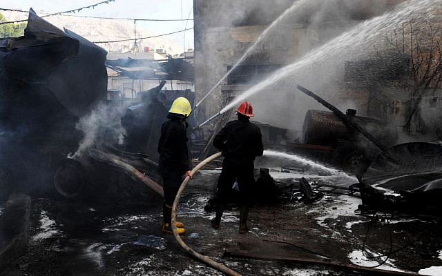 Firefighters extinguish fire at the scene after a bomb attached to a fuel truck exploded outside a Damascus hotel in August (illustrative photo credit: AP/SANA)