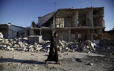 A man walks by a destroyed building in Azaz near Aleppo last week. (photo credit: AP/Muhammed Muheisen)