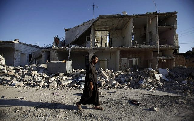 A man walks by a destroyed building in Azaz near Aleppo last week. (photo credit: AP/Muhammed Muheisen)