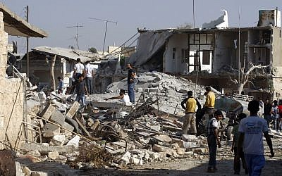 Syrians check the damage of destroyed houses after an air strike destroyed at least ten houses in the town of Azaz on the outskirts of Aleppo, Syria on Wednesday (photo credit: AP/Khalil Hamra)